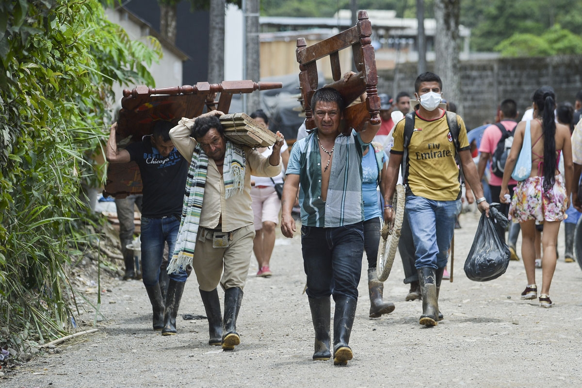 Locals walk carrying recovered belongings following mudslides caused by heavy rains in Mocoa, Putumayo department, southern Colombia on April 2, 2017.