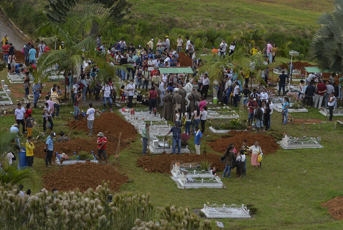 People attend the mass burial of the victims of a mudslide caused by heavy rains, at the cemetery in Mocoa, Putumayo department, Colombia on April 3, 2017.
