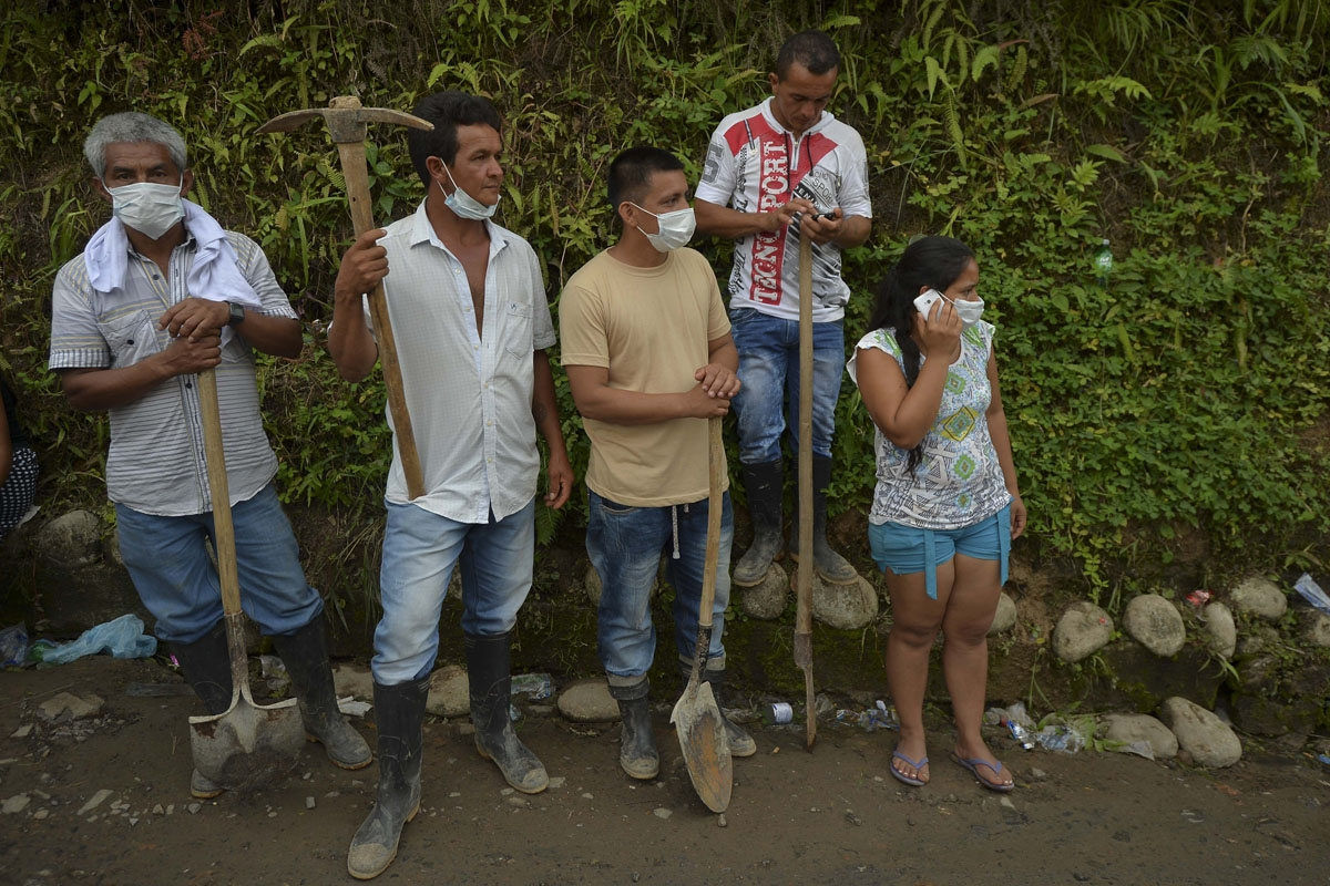 People with tools wait to enter the cemetery and bury their relatives, victims of a mudslide caused by heavy rains, at the cemetery in Mocoa, Putumayo department, Colombia on April 3, 2017.