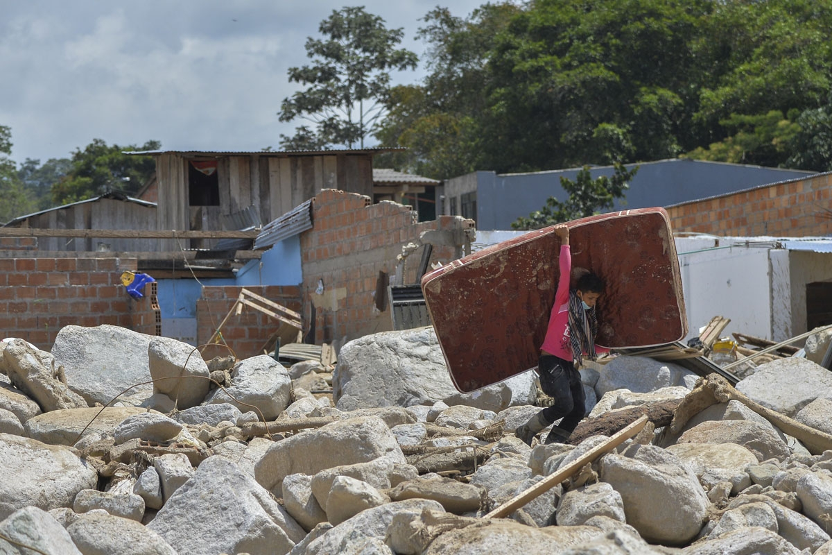 A young man carries a mattress amid the rubble left by mudslides caused by heavy rains in Mocoa, Putumayo department, southern Colombia on April 4, 2017.