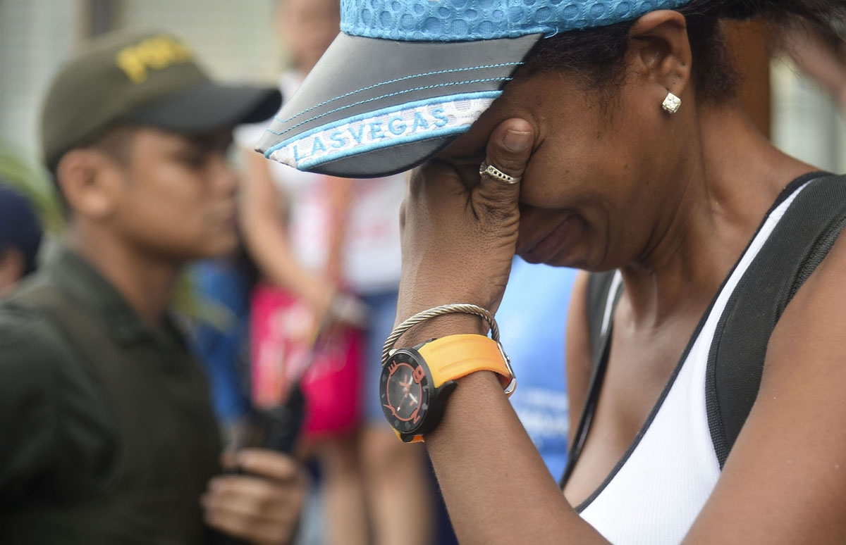 A Cuban migrant cries before boarding a vessel to Capurgana, in the Caribbean Gulf of Uraba in northwestern Colombia, to illegally cross to Panama through the jungle, on August 6, 2016