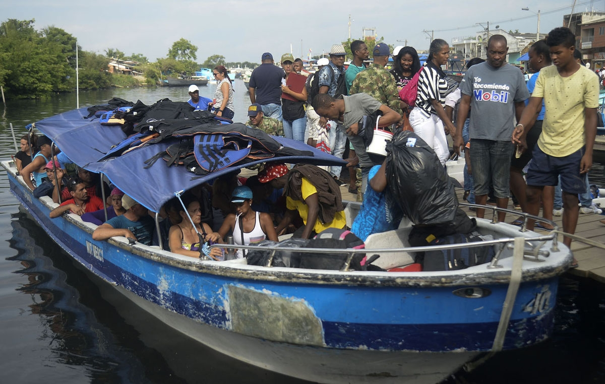 Cuban and Haitian migrants board a vessel to Capurgana, in the Caribbean Gulf of Uraba in northwestern Colombia, to illegally cross to Panama through the jungle, on August 6, 2016