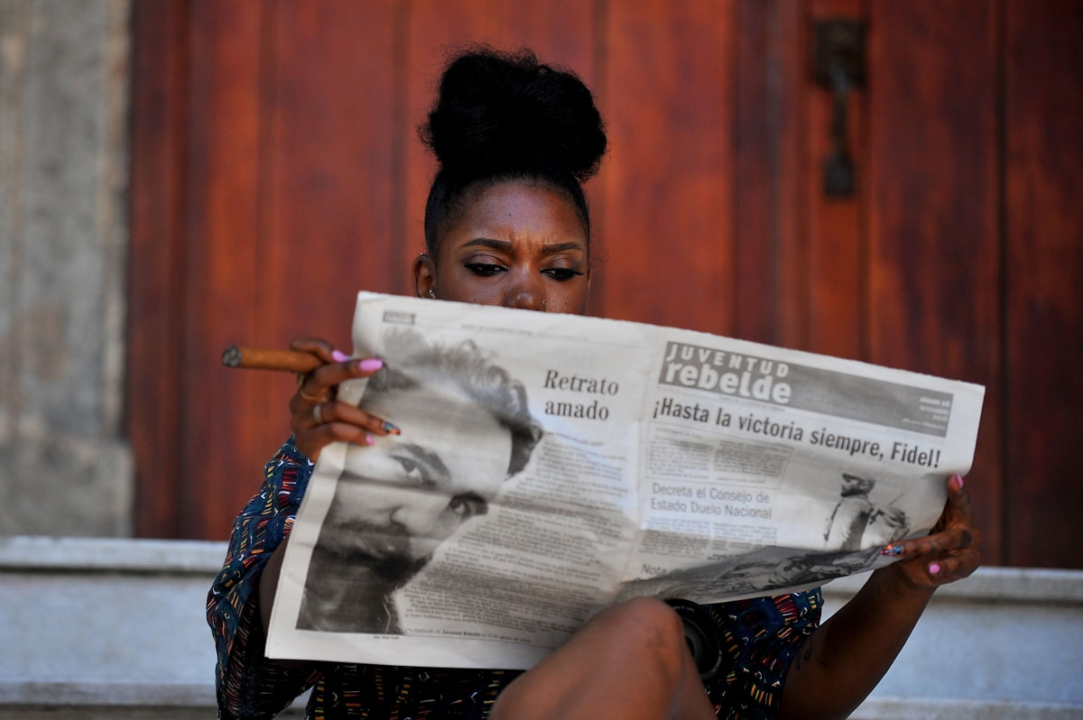A woman smokes a cigar as she reads the newspaper in a street of Havana, on November 26, 2016, the day after Cuban revolutionary leader Fidel Castro died aged 90.