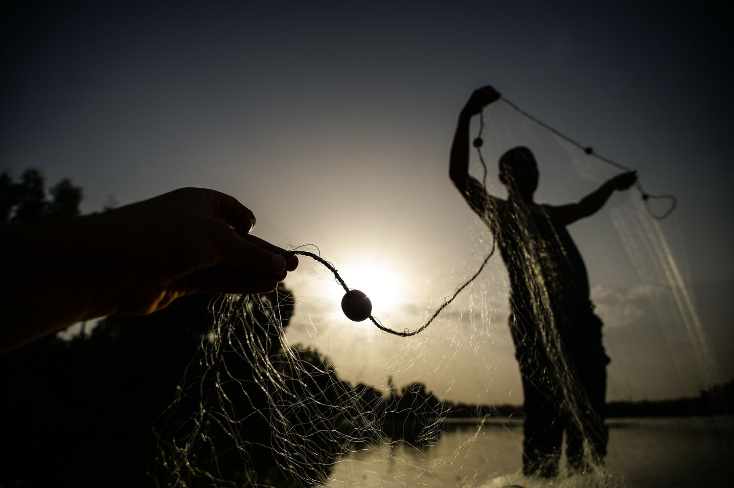 An Egyptian Fisherman handles a net on his boat in the waters of the Pharaonic Sea in the village of Kafr Fisha, province of Munuf, on June 16, 2018. The Pharaonic Sea is the name of a large water body in the province of Menoufia, an area of 2500 acres an