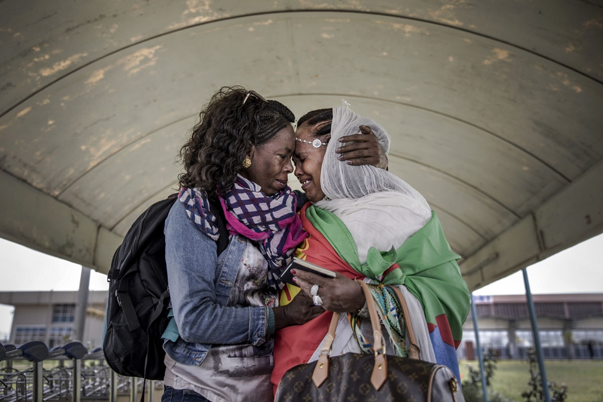 Two Eritrean sisters living in the diaspora get reunited in their home country after more than two decades without seeing each other upon the arrival of the flight from Ethiopian capital Addis Ababa at Asmara International Airport in Asmara, Eritrea on Ju