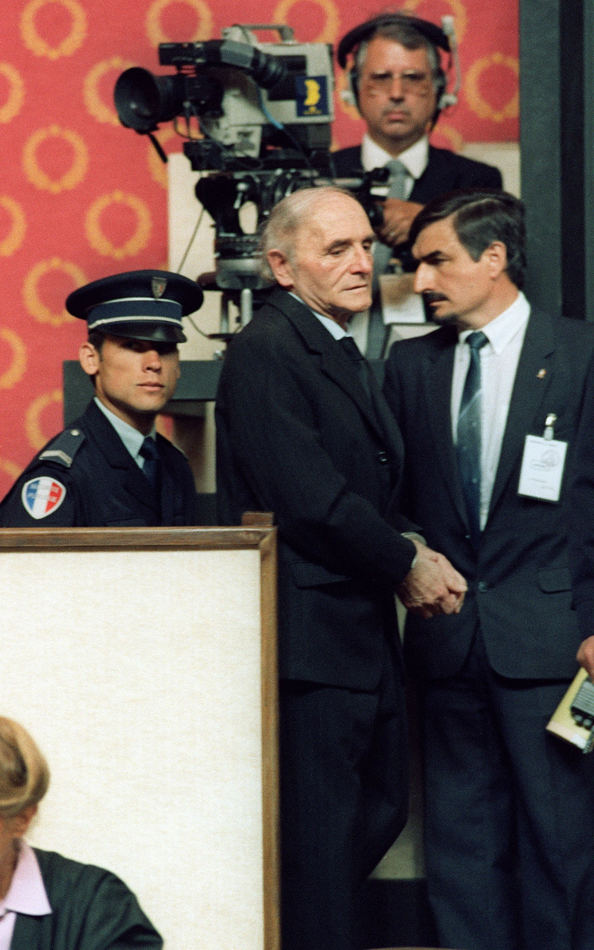 Former SS officer Klaus Barbie, the Butcher of Lyons, in handcuffs, arrives at the courthouse, in Lyons, 11 May 1987 o