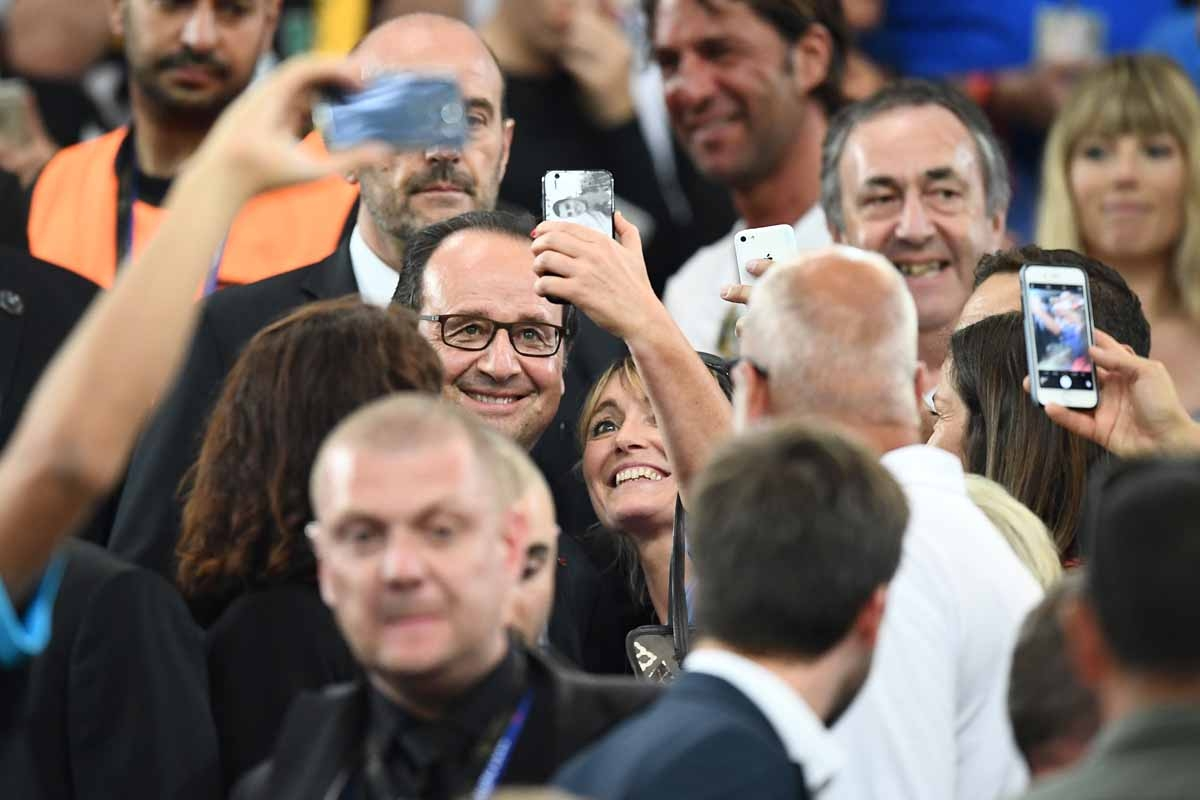 French President Francois Hollande poses for selfies at the end of the Euro 2016 semi-final football match between Germany and France at the Stade Velodrome in Marseille on July 7, 2016. France will face Portugal in the Euro 2016 finals on July 10, 2016.