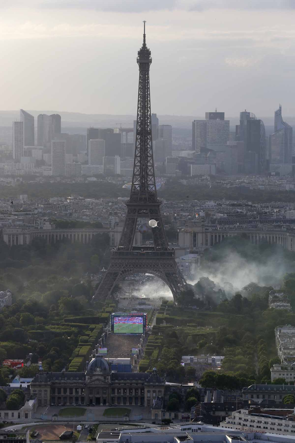 A picture taken from the Tour Montparnasse shows tear gas under the Eiffel tower during clashes between police and supporters trying to illegally enter the Champs de Mars fan zone on July 10, 2016 in Paris, before the Euro 2016 football tournament final m