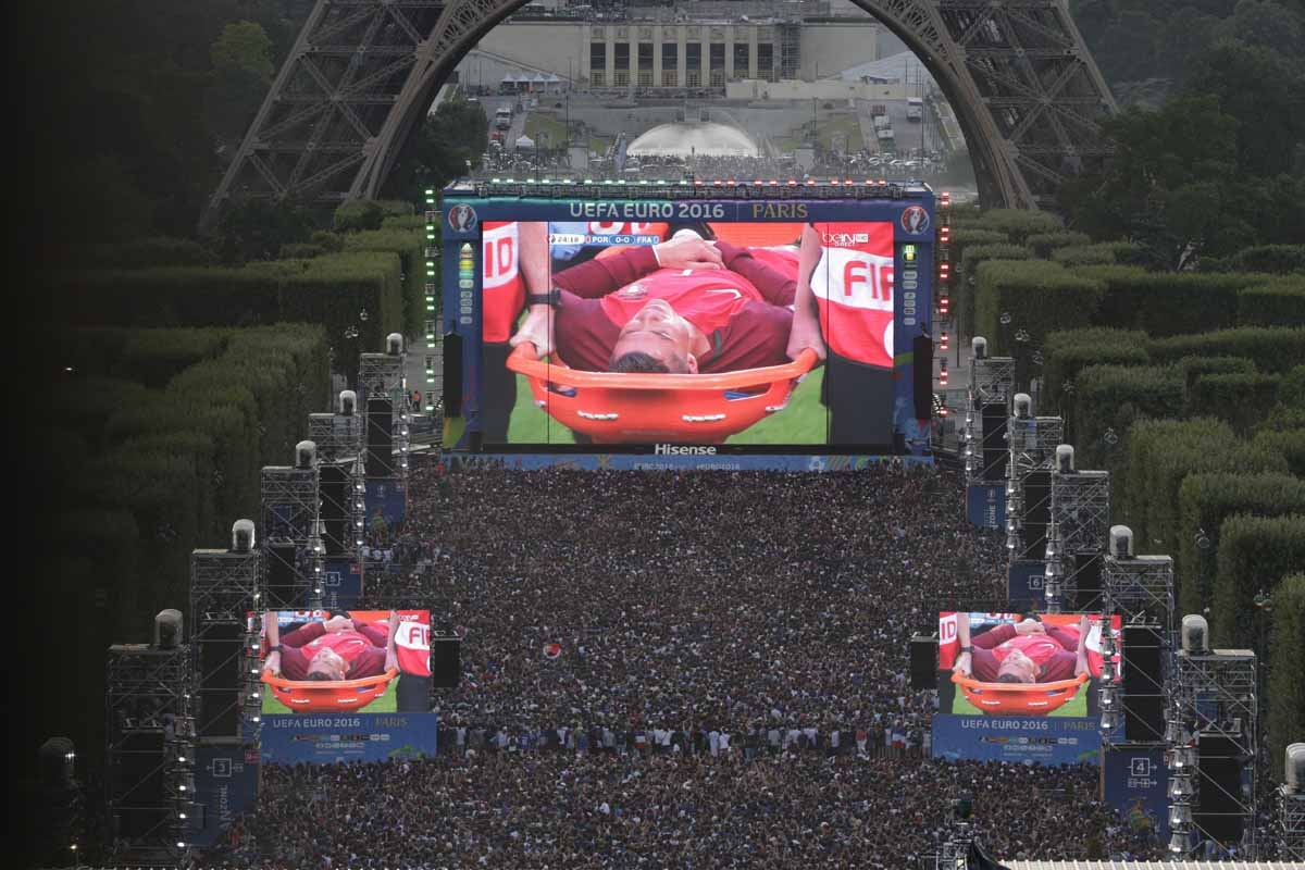 People watch on a giant screen the Euro 2016 football tournament final match between Portugal and France, while Portuguese forward Cristiano Ronaldo is evacuated on a stretcher after being injured, on July 10, 2016 at the fan zone of the Champs de Mars ne