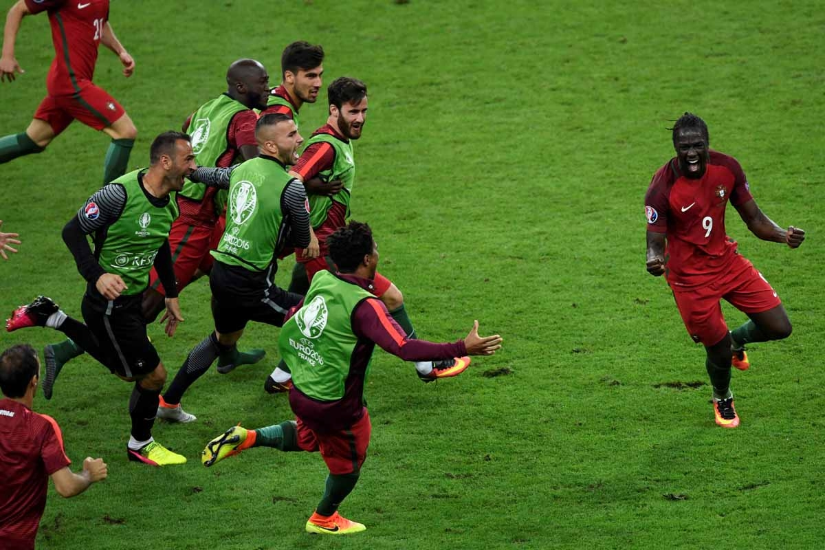 Portugal's forward Eder (R) celebrates after scoring a goal with team mates during the Euro 2016 final football match between Portugal and France at the Stade de France in Saint-Denis, north of Paris, on July 10, 2016. / AFP PHOTO / MIGUEL MEDINA
