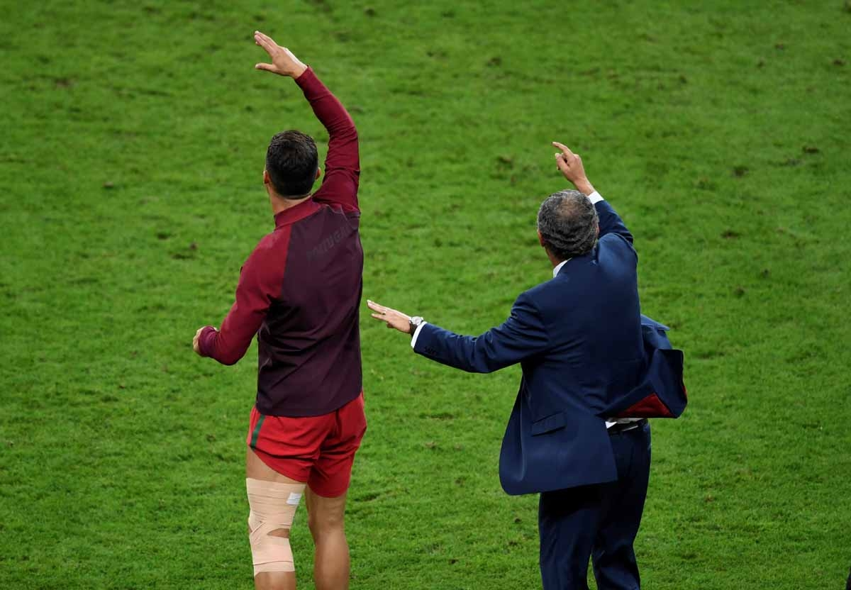 Portugal's forward Cristiano Ronaldo (L) and Portugal's coach Fernando Santos celebrate their team's win in the Euro 2016 final football match between Portugal and France at the Stade de France in Saint-Denis, north of Paris, on July 10, 2016. / AFP PHOTO