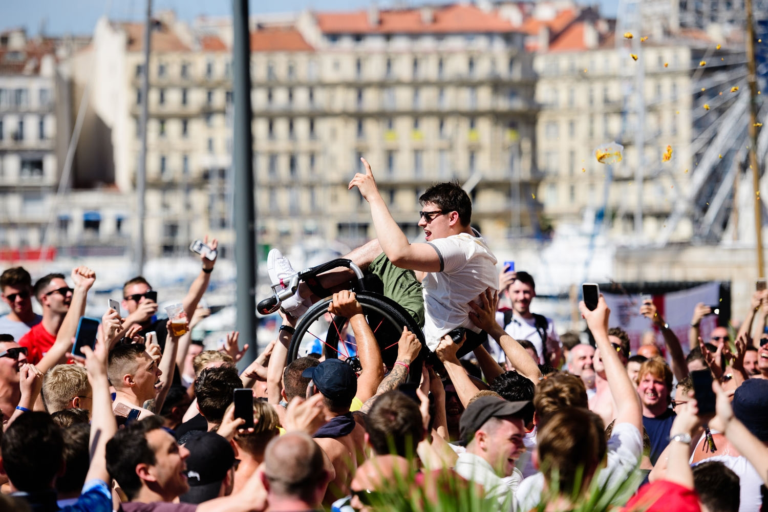 A man in a wheelchair is lifted into the air by England fans as they gather in Marseille, southern France, on June 10, 2016