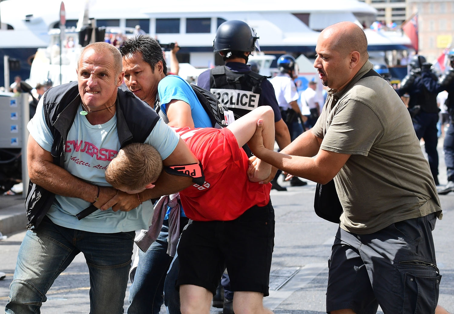 An England fan (C) is detained by police personnel following clashes between England fans and police in the city of Marseille, southern France, on June 11, 2016