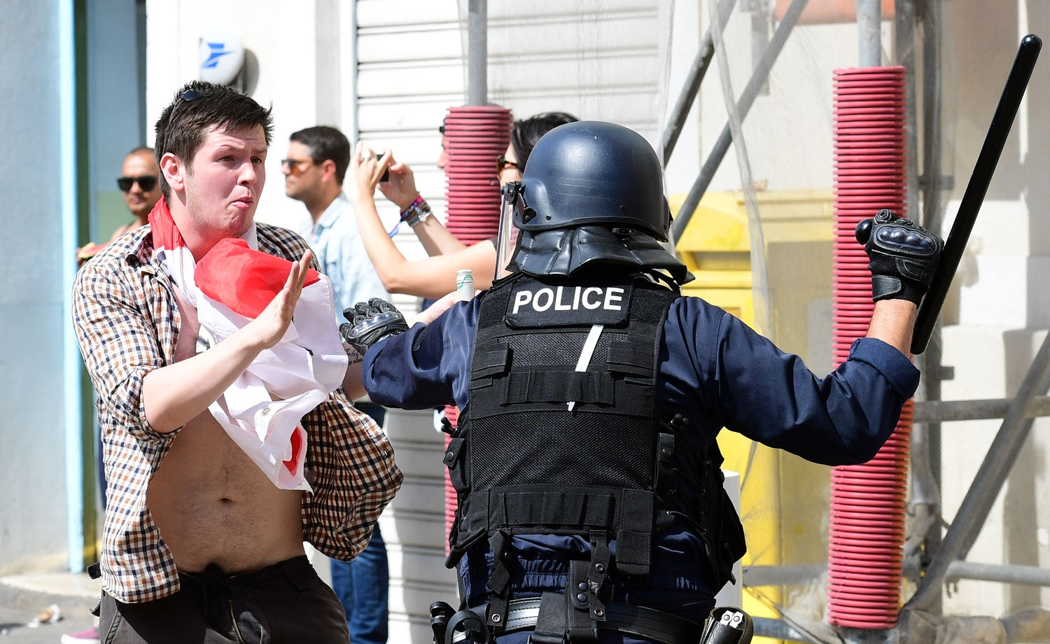 An England fan (L) clashes with police personnel in the city of Marseille, southern France, on June 11, 2016