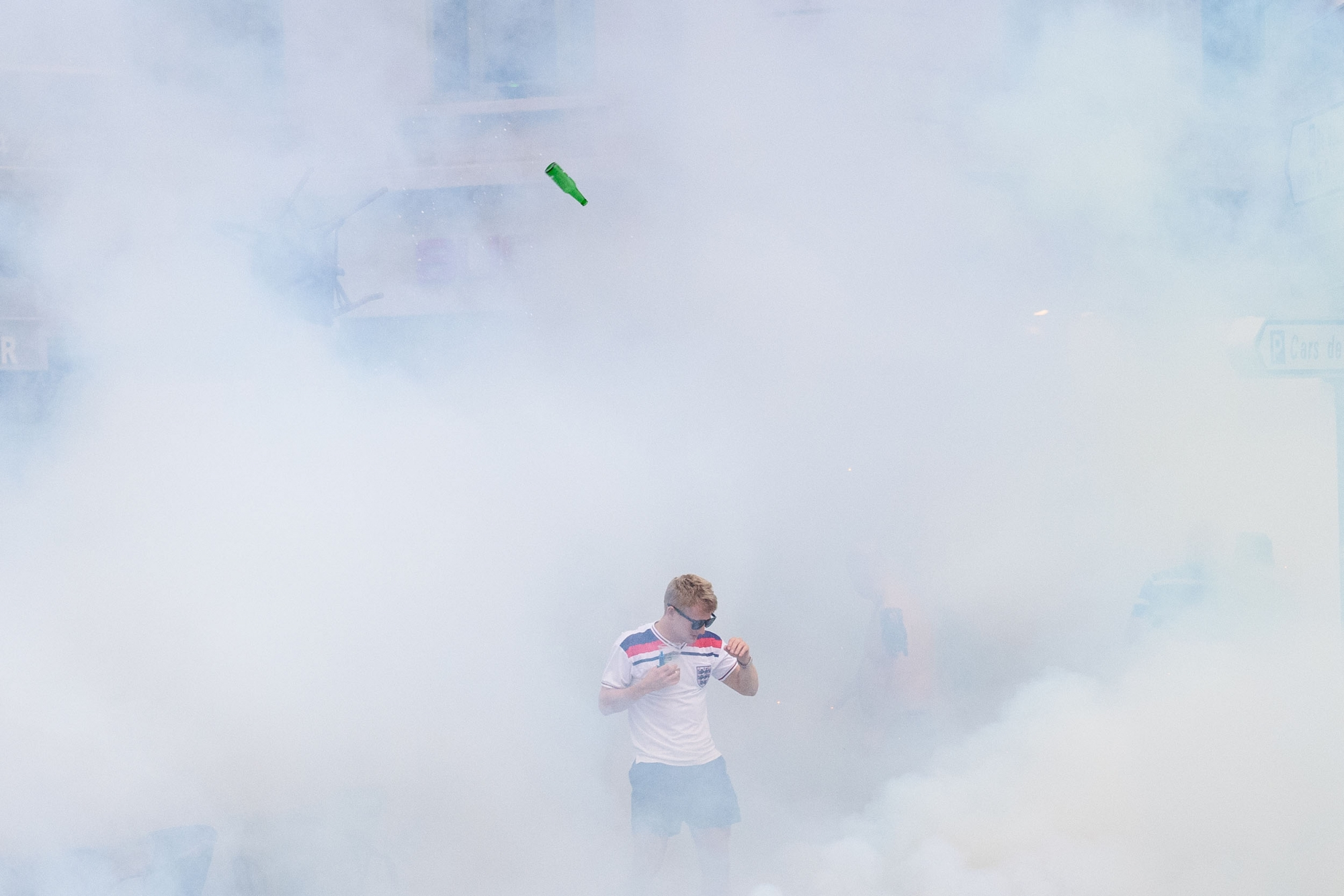 An England supporter walks as he is engulfed in tear gas during clashes with police in Marseille, southern France, on June 10, 2016