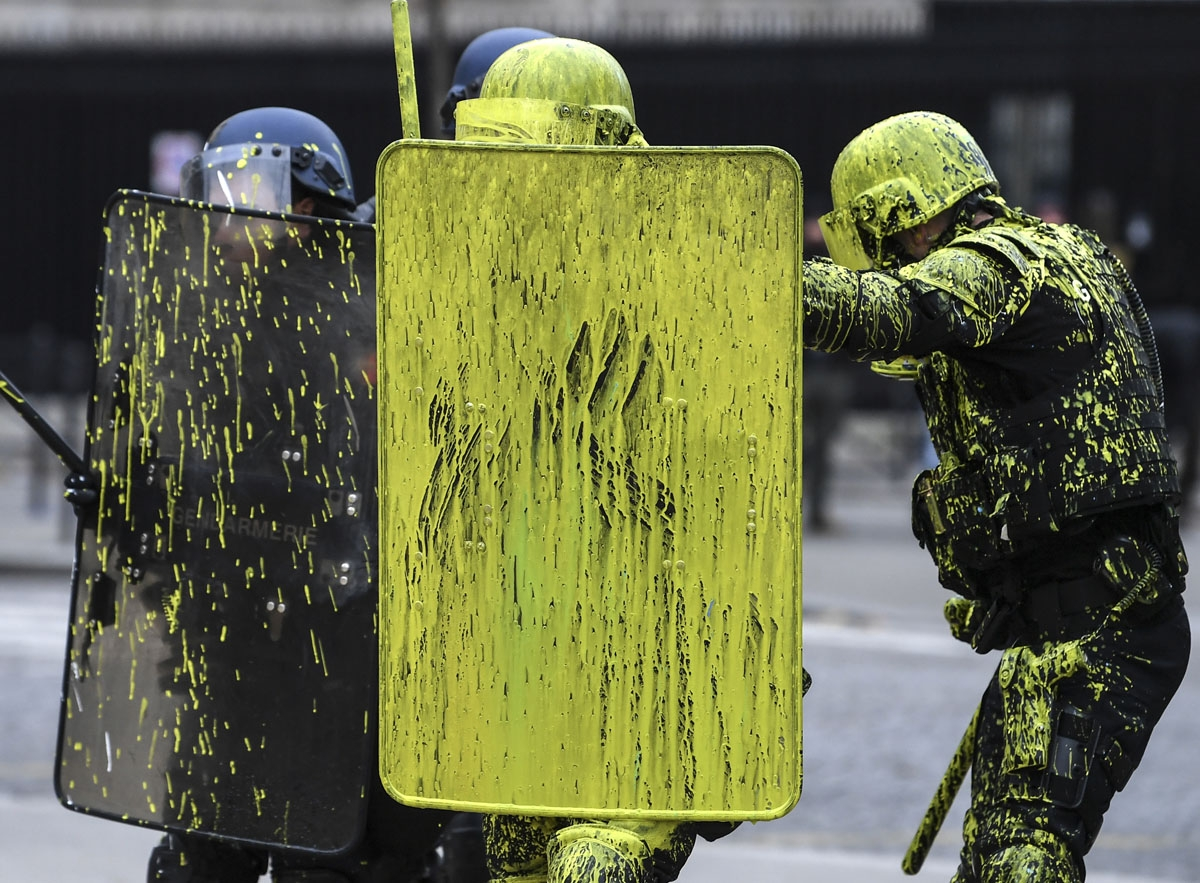 Riot police officers are covered with painting during clashes with demonstrators as part of a protest of Yellow vests (Gilets jaunes) against rising oil prices and living costs on the Champs Elysees in Paris, on December 1, 2018. -