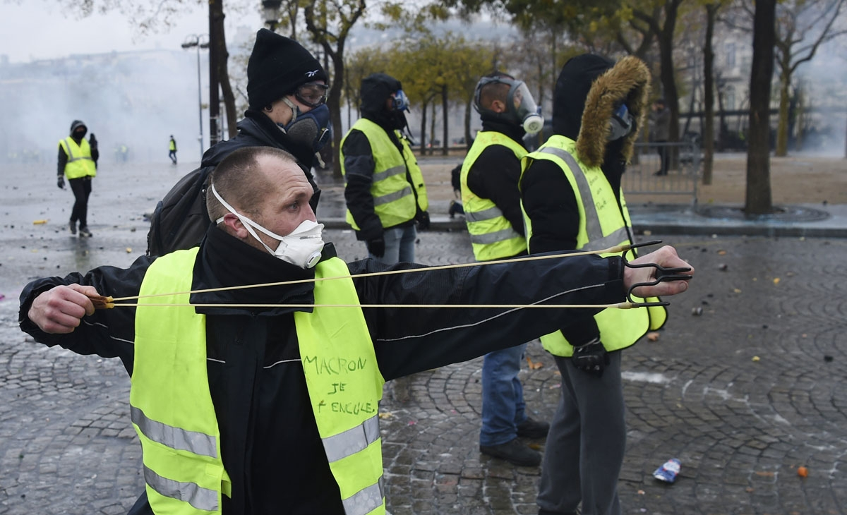 A demonstrator uses a slingshot to throw projectiles at police during a protest of Yellow vests (Gilets jaunes) against rising oil prices and living costs, on the Champs Elysees avenue in Paris on December 1, 2018. -