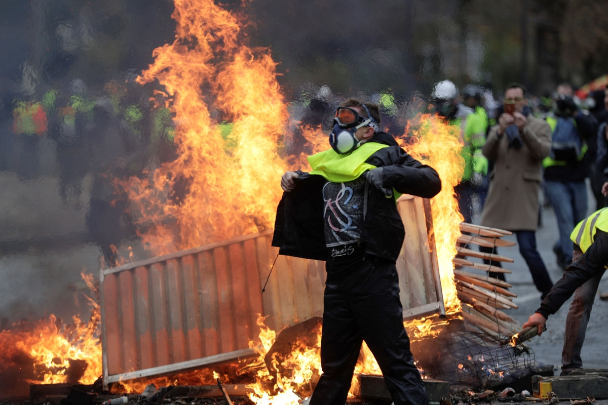 A demonstrator walks past a fire during a protest of Yellow vests (Gilets jaunes) against rising oil prices and living costs on the Champs Elysees, in Paris, on December 1, 2018. -