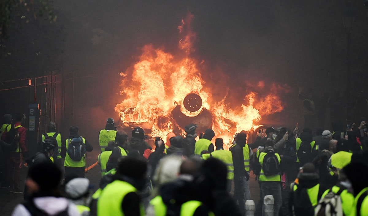 Demonstrators stand in front of a burning car during a protest of Yellow vests (Gilets jaunes) against rising oil prices and living costs, on December 1, 2018 in Paris.