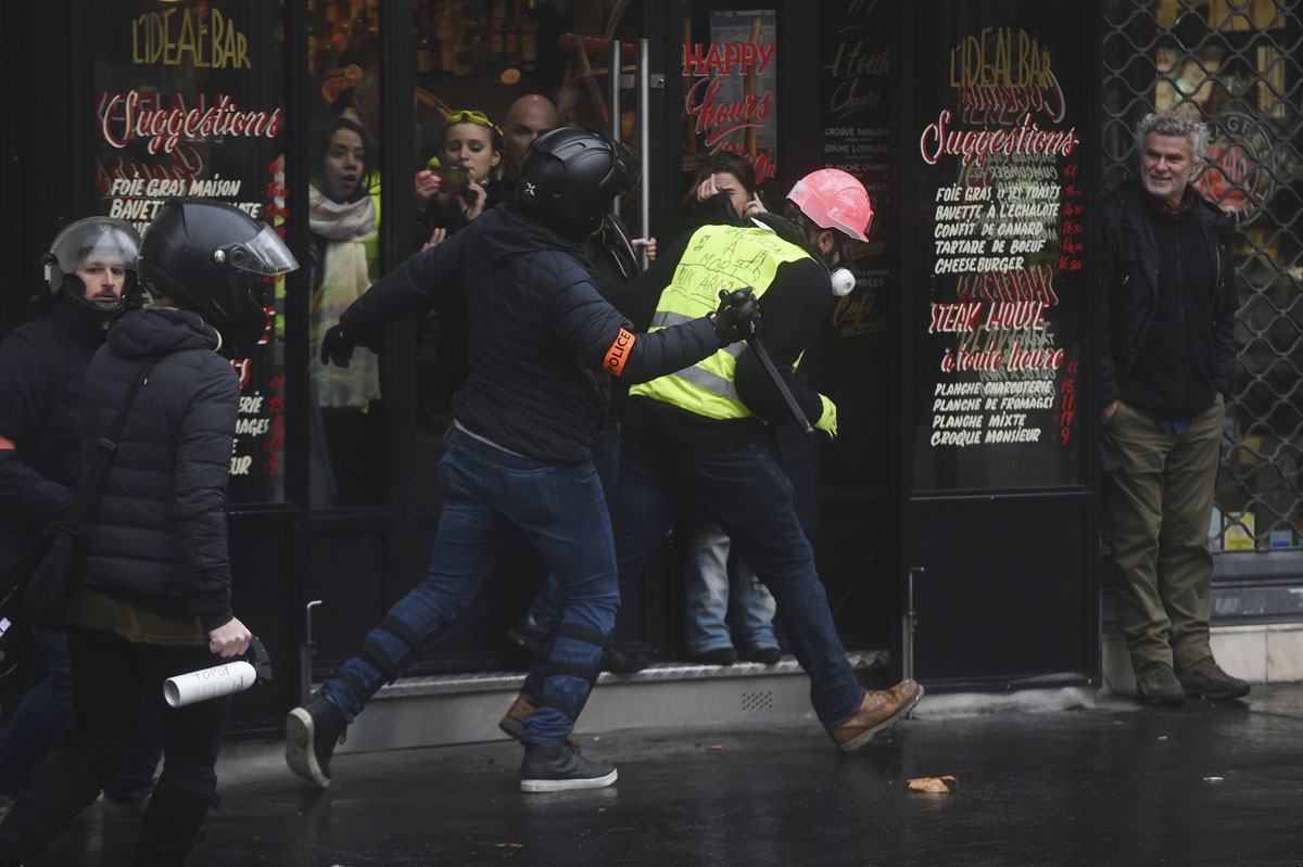 Riot police officers clash with demonstrator during a protest of Yellow vests (Gilets jaunes) against rising oil prices and living costs, on December 1, 2018 in Paris.