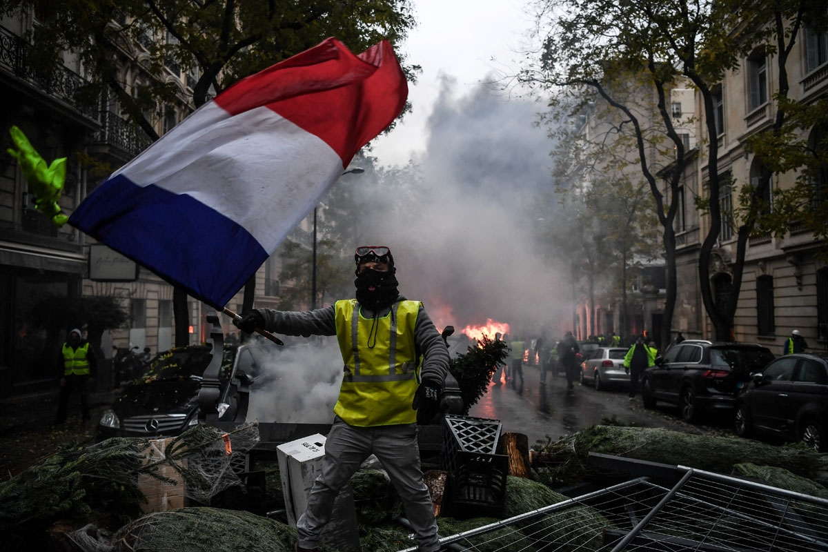 demonstrator holds a French flag during a protest of Yellow vests (Gilets jaunes) against rising oil prices and living costs, on December 1, 2018 in Paris. - Speaking at the Paris police's command centre, French Prime Minister said 36,000 people were prot