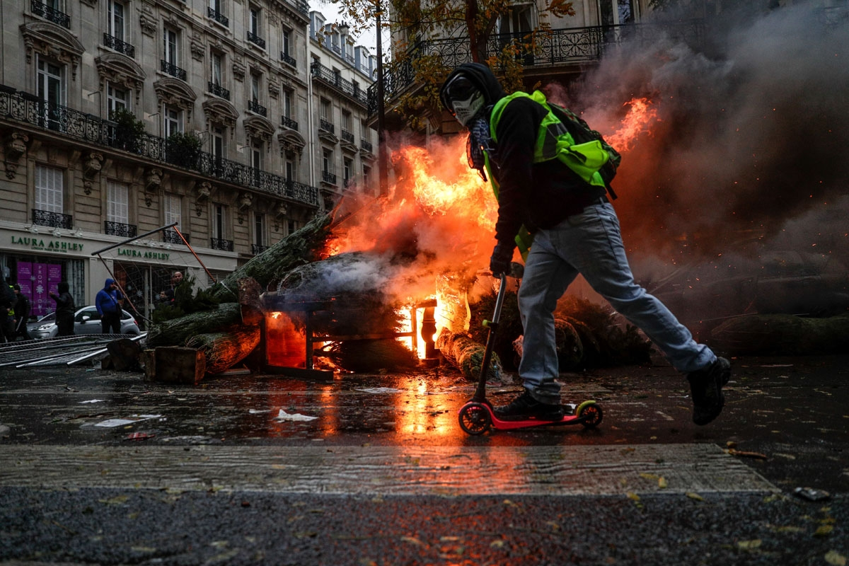 A demonstrator rides past a fire during a protest of Yellow vests (Gilets jaunes) against rising oil prices and living costs, on December 1, 2018 in Paris. - Speaking at the Paris police's command centre, French Prime Minister said 36,000 people were prot