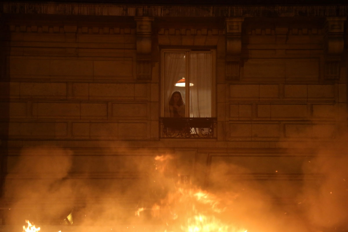 A inhabitants looks at flames from her window during a demonstration by Yellow Vests (Gilets Jaunes in French) against rising oil prices and living costs, at Bastille in the French capital Paris on December 1, 2018.