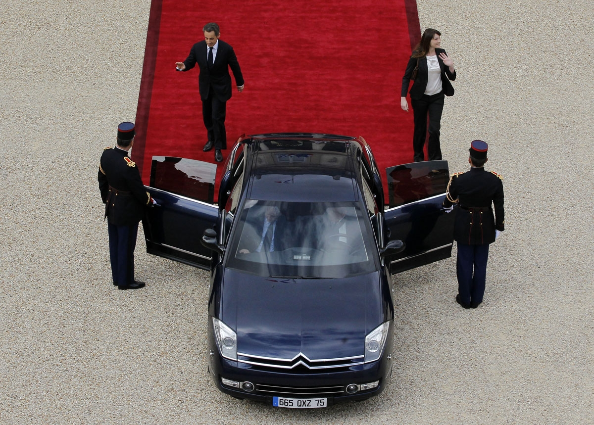 Former France's president Nicolas Sarkozy (L) and his wife Carla Bruni-Sarkozy leave the Elysee presidential Palace after the formal investiture ceremony between France's president-elect Francois Hollande and his predecessor Nicolas Sarkozy, on May 15, 20