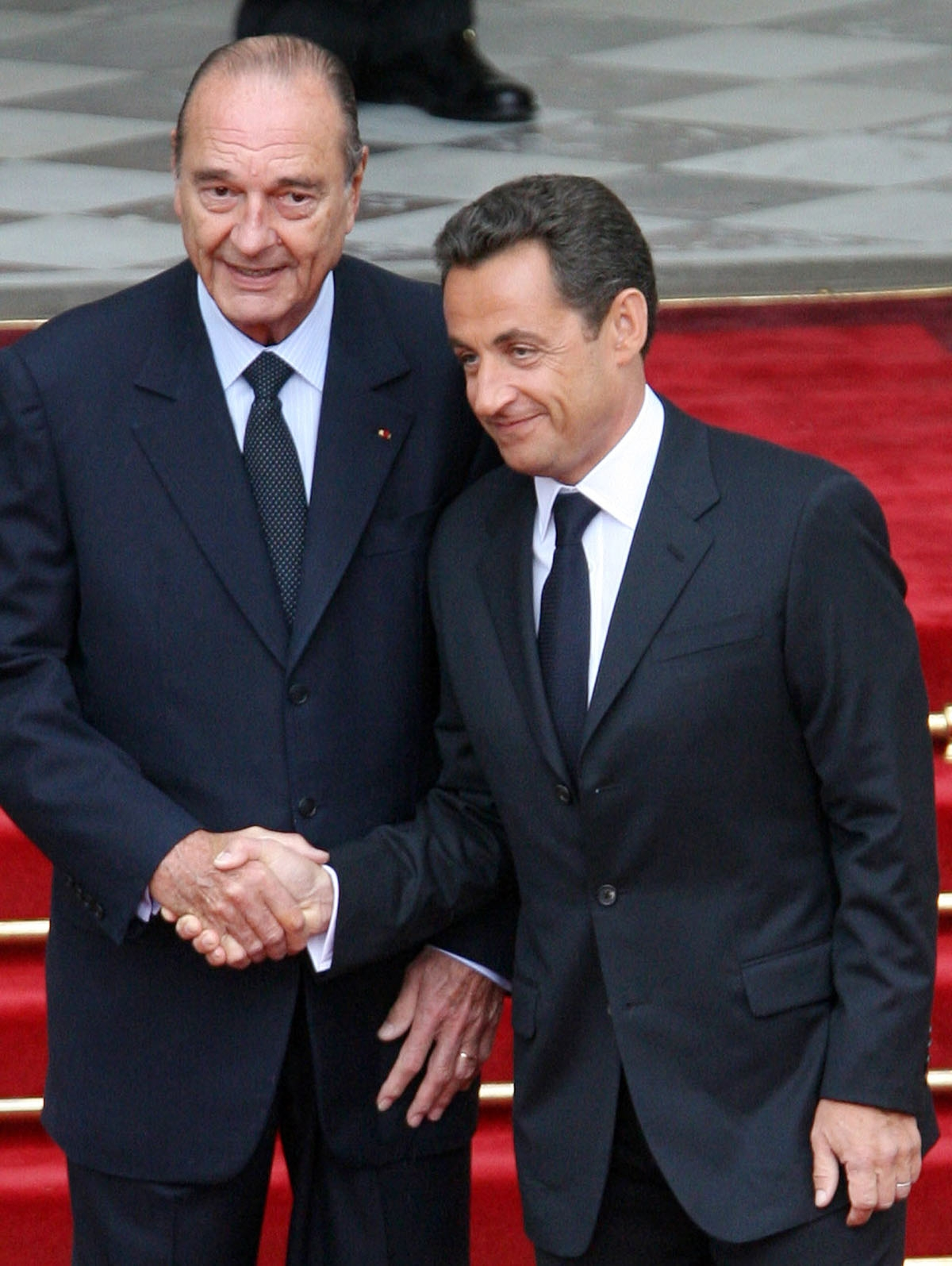 French president Jacques Chirac (L) welcomes his  successor Nicolas Sarkozy upon his arrival at the Elysee Palace for the formal handover of power ceremony, 16 May 2007 in Paris