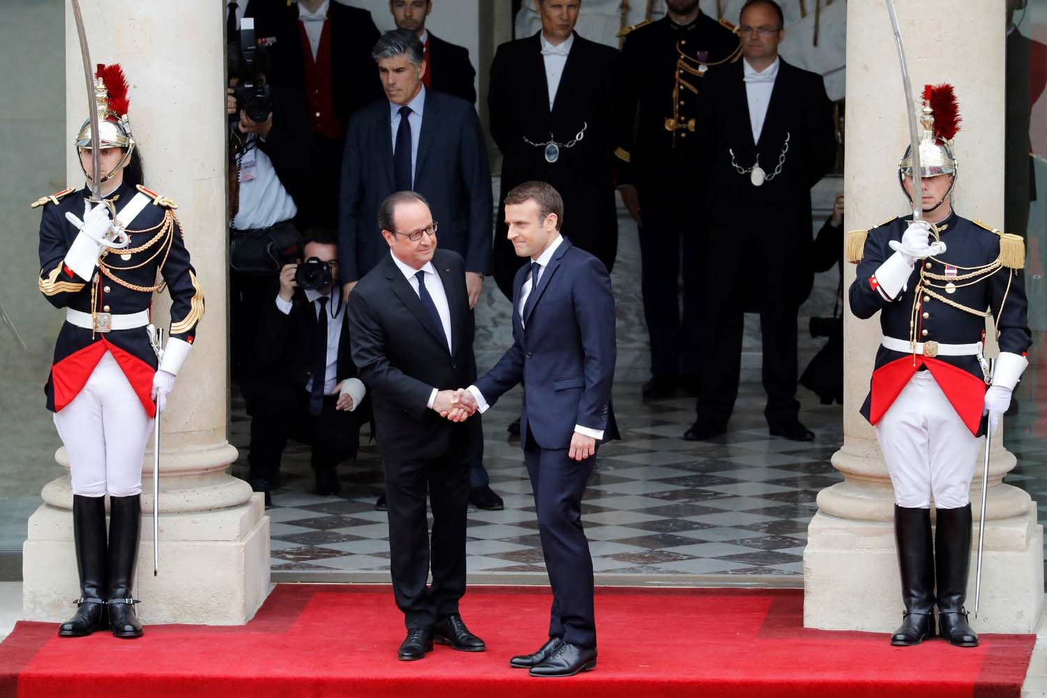 French newly elected President Emmanuel Macron (R) is welcomed by his predecessor Francois Hollande as he arrives at the Elysee presidential Palace for the handover and inauguration ceremonies on May 14, 2017 in Paris. / AFP PHOTO / POOL / Patrick KOVARIK