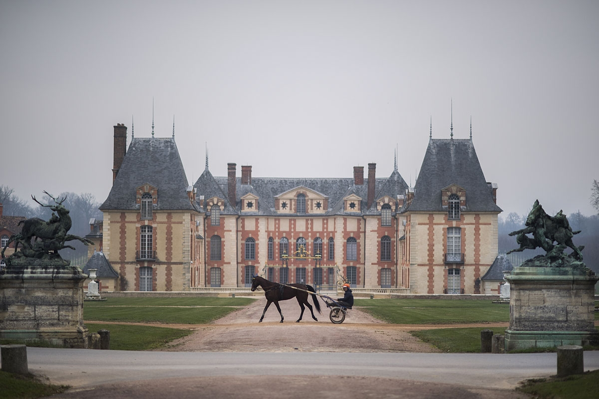 A horse and its driver walk past the castle of Grobois at the equestrian training center of Grosbois in Marolles-en-Brie, on December 2, 2016.