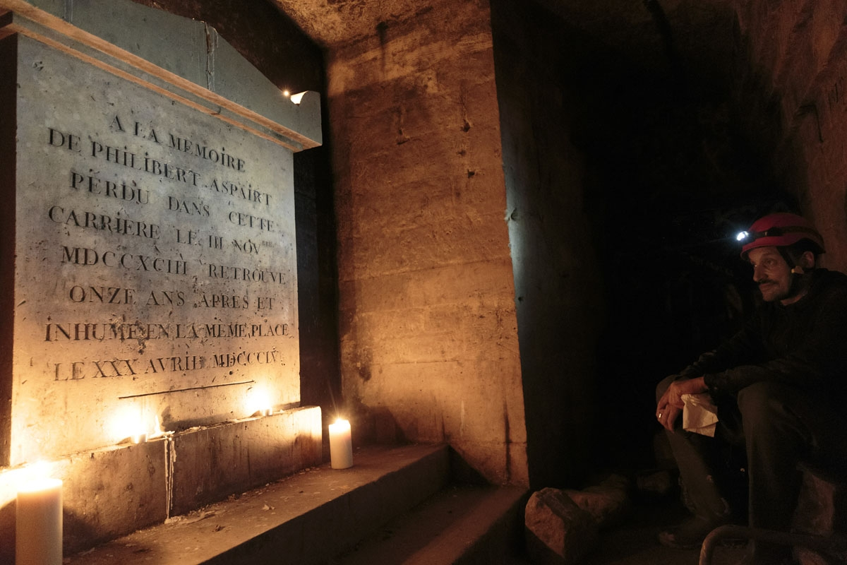 This photograph taken on November 7, 2017, shows Pascal, 36 as he pays his respects to the patron saint of cataphiles, Philibert Aspairt besides his grave in the banned catacombs of Paris.