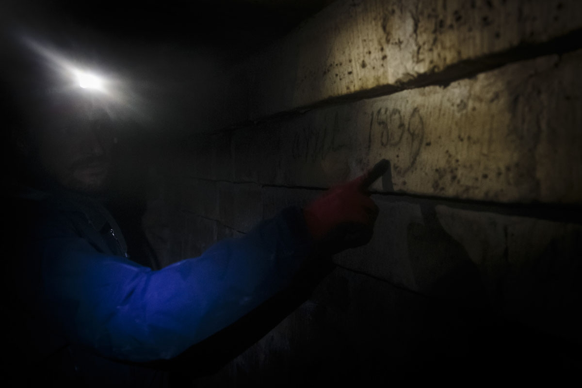In this photograph taken on October 31, 2017,  Pascal, 36, indicates a date on a wall in the banned catacombs of Paris.