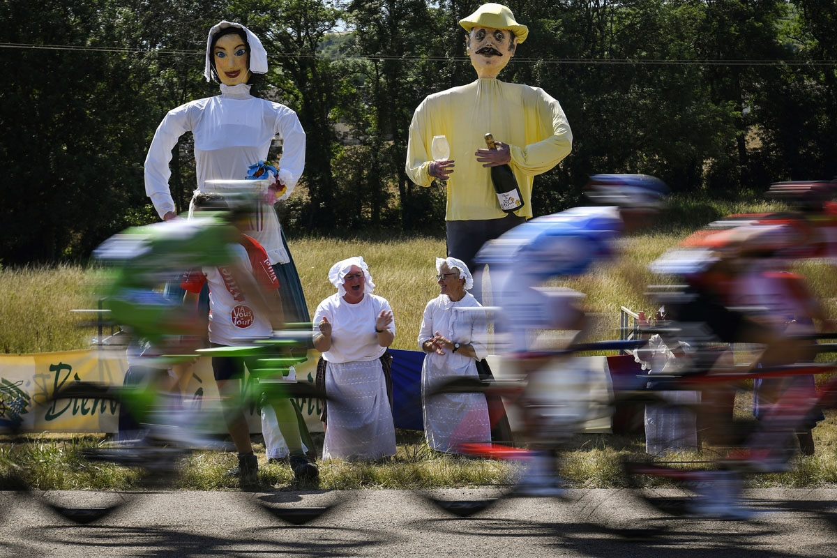 . Giants statues are pictured along the road as woman cheer during the 216 km sixth stage of the 104th edition of the Tour de France cycling race on July 6, 2017 between Vesoul and Troyes