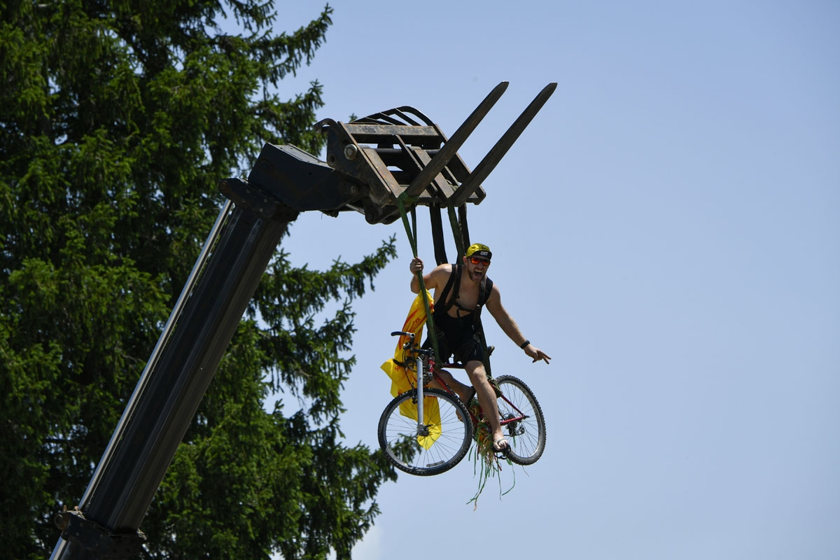 A supporter sits on a bike suspended from a crane along the road during the 187,5 km eighth stage of the 104th edition of the Tour de France cycling race on July 8, 2017 between Dole and Station des Rousses.