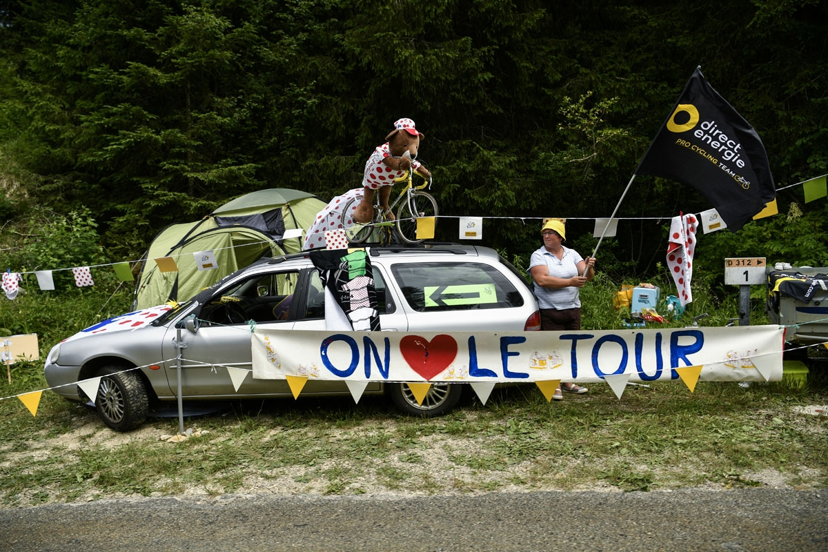 A supporter waves a flag of the France's Direct Energie cycling team behind a banner reading We love the Tour de France during the 187,5 km eighth stage of the 104th edition of the Tour de France cycling race on July 8, 2017 between Dole and Station des R