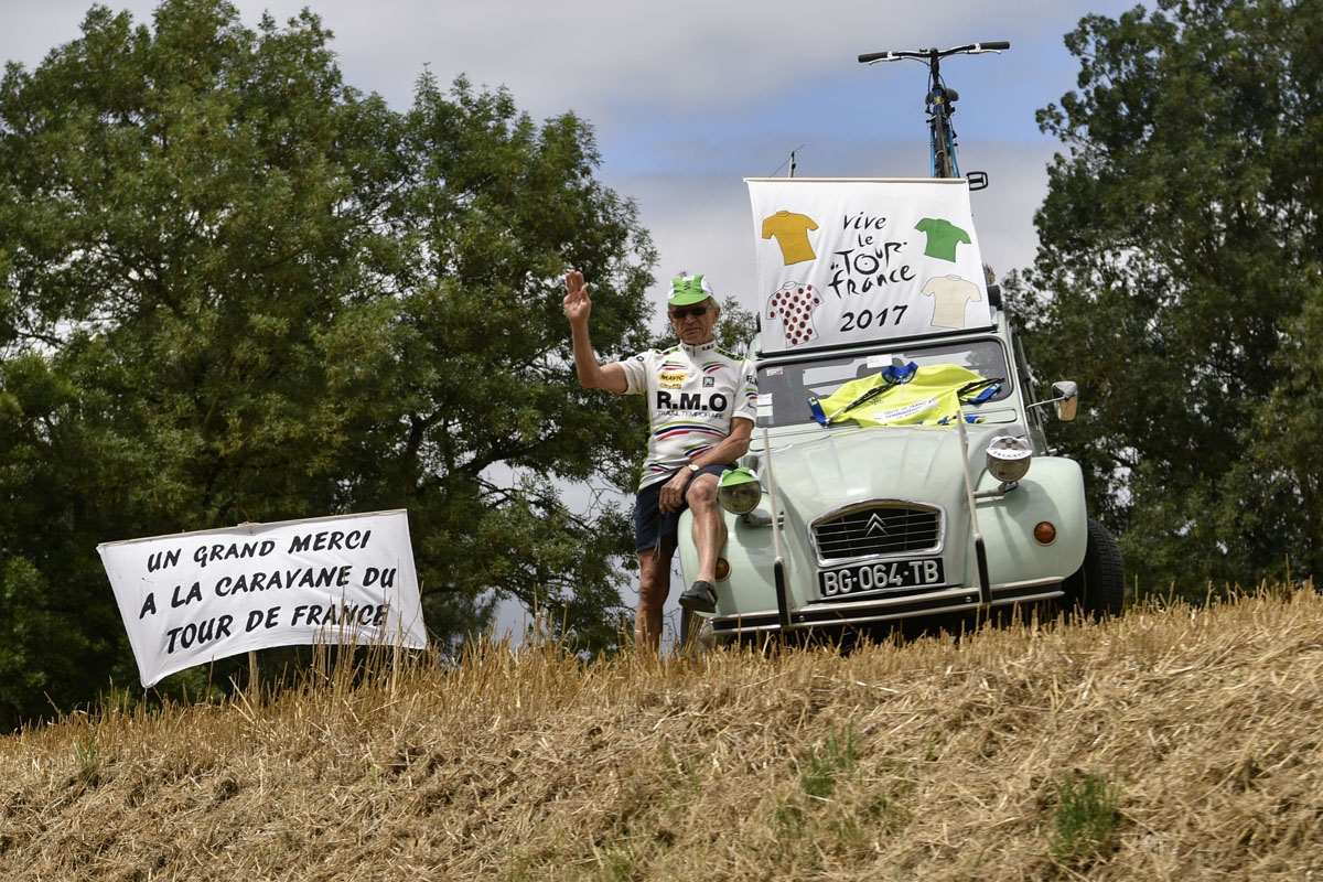 A supporter cheers along the road near placards reading A big thank you to the caravan of the Tour de France (L) and Long life the Tour de France during the 203,5 km eleventh stage of the 104th edition of the Tour de France cycling race on July 12, 2017 b