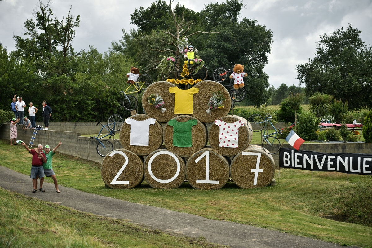 Supporters cheer along the road next to a placard reading Welcome (R) during the 203,5km eleventh stage of the 104th edition of the Tour de France cycling race on July 12, 2017 between Eymet and Pau