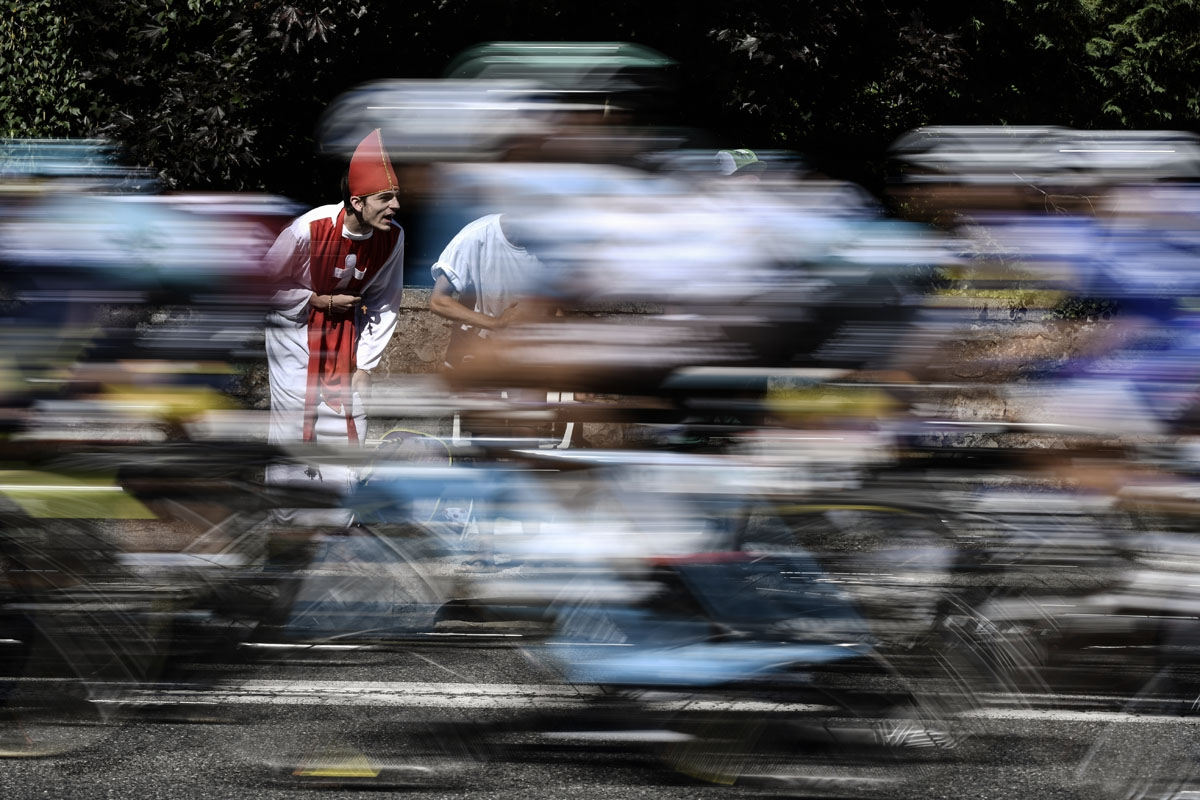 A supporter disguised as a priest cheers as the pack rides during the 181,5 km fourteenth stage of the 104th edition of the Tour de France cycling race on July 15, 2017 between Blagnac and Rodez