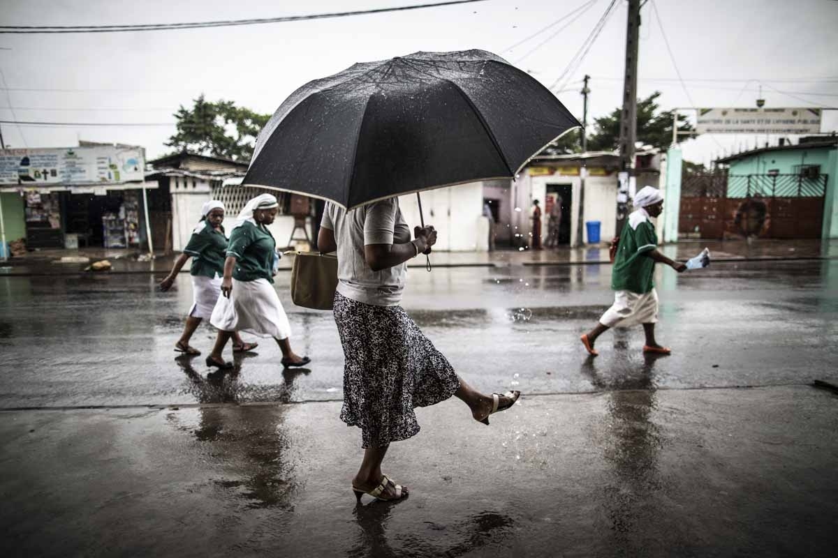 A woman washes a her foot with water streaming out of a pipe as catholic nuns leave the St. Michel Church in Libreville on August 28, 2016 after the Sunday's service.