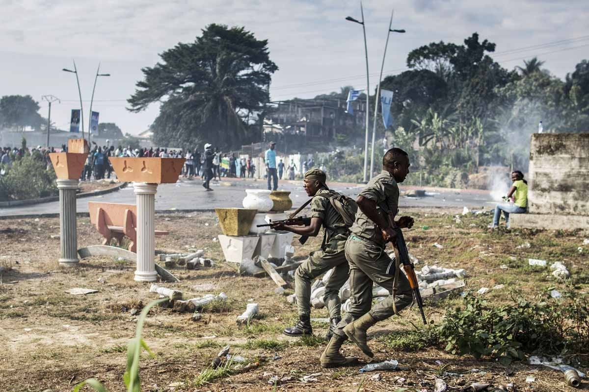 Gabonese soldiers run to take position as supporters of opposition leader Jean Ping protest in front of security forces blocking a demonstration trying to reach the electoral commission in Libreville on August 31, 2016.
