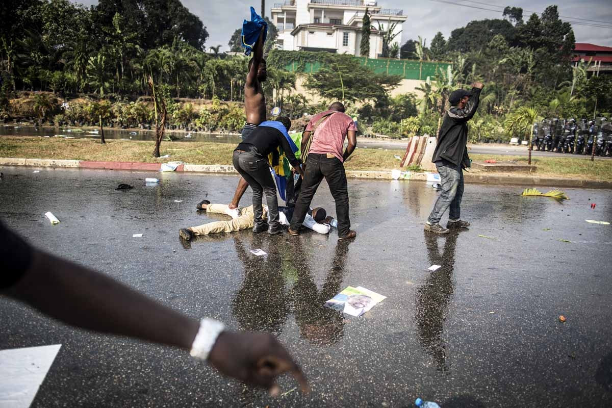 A supporter of Gabonese opposition leader Jean Ping lies on the ground in Libreville on August 31, 2016, during clashes with riot police as part of a protest sparked after Gabon's president Ali Bongo was declared winner of last weekend's contested electio