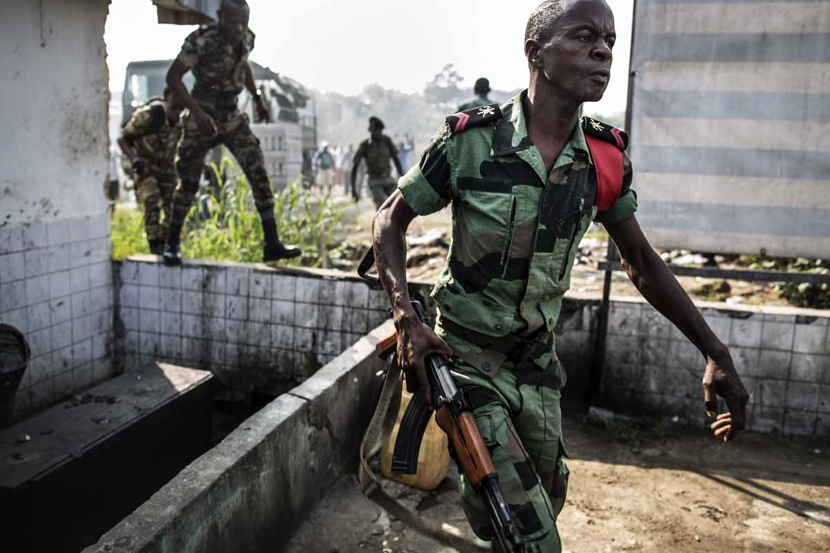 A Gabonese soldier runs to take position as supporters of opposition leader Jean Ping protest in front of security forces blocking the demonstration trying to reach the electoral commission, in Libreville on August 31, 2016, as part of a protest sparked a