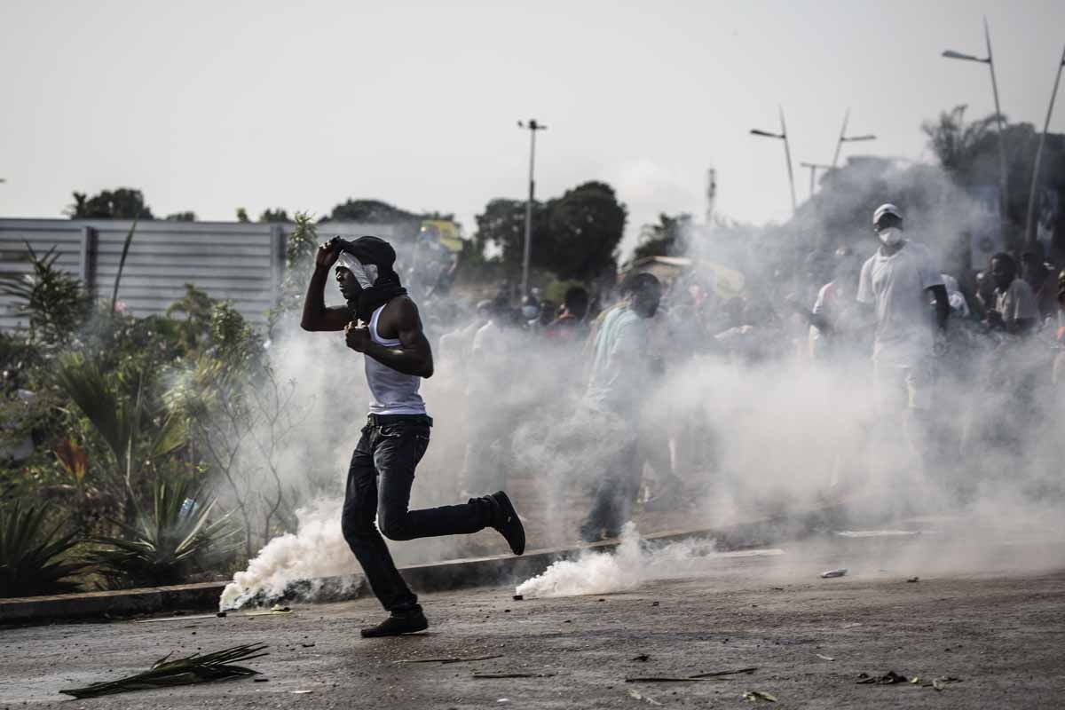 A protester runs amid tear gas canisters during confrontations with the police in Libreville on August 31, 2016 as part of a protest sparked after Gabon's president Ali Bongo was declared winner of last weekend's contested election.