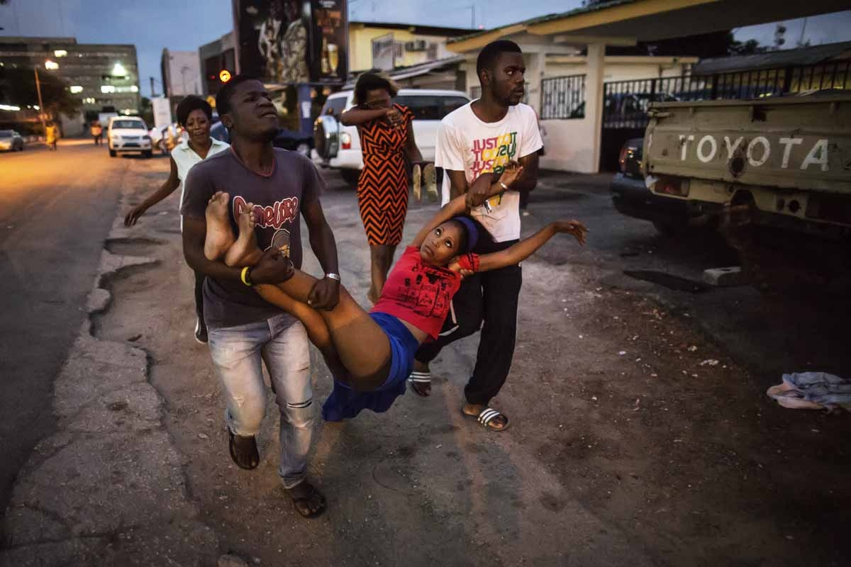 A relative a man detained during clashes is carried to the hospital after she fainted on September 1, 2016 in Libreville.