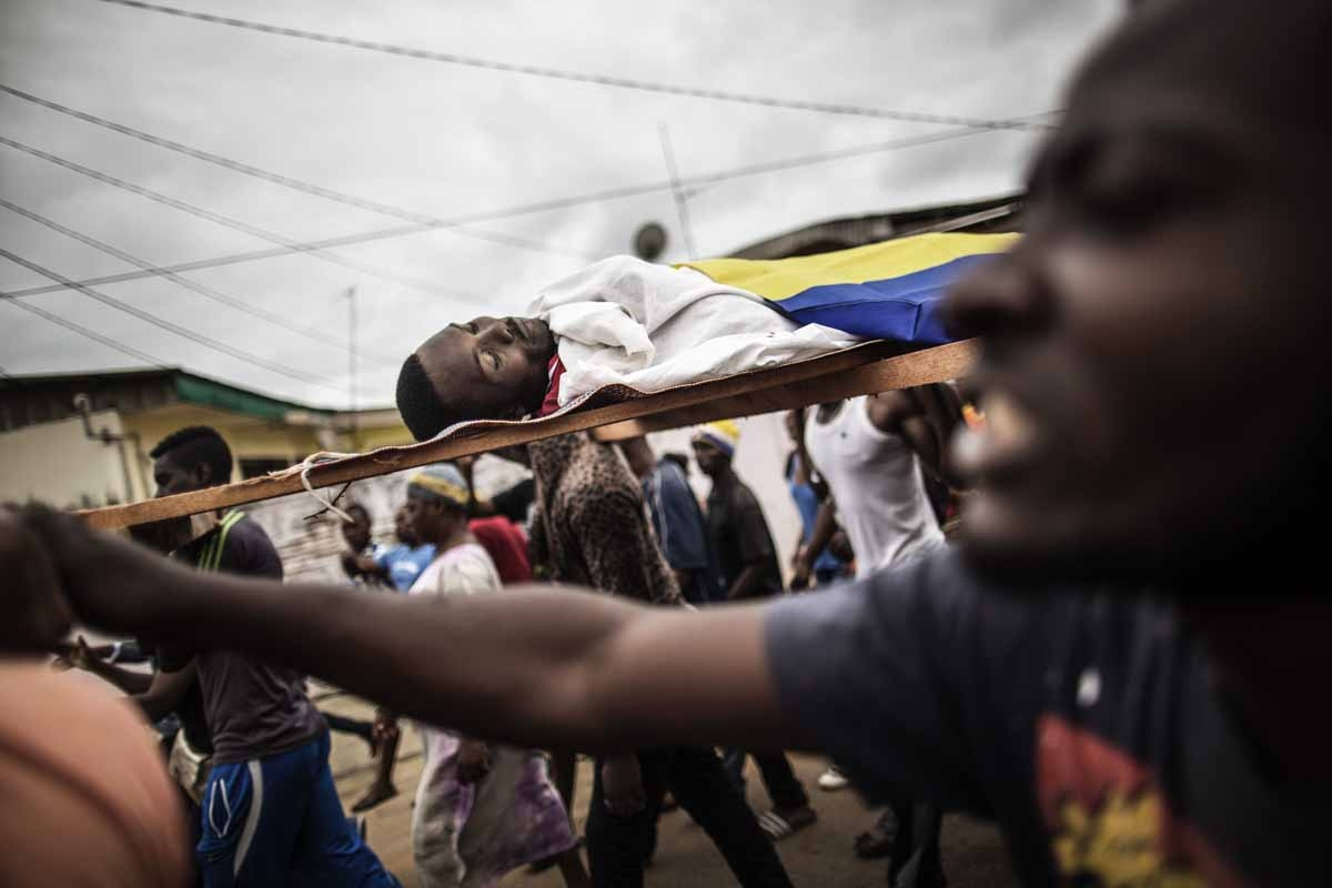 Dozens of protesters carry in a funeral procession the body of Axel Messa, 30, wrapped in the flag of Gabon, in a street of the Libreville district of Nzeng Ayong on September 2, 2016. His mother told AFP he was shot in front of his home on September 1, 2