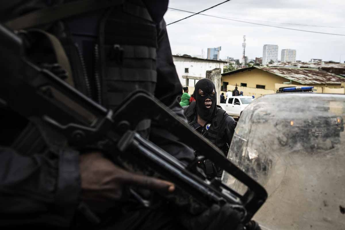 Gabonese police officers secure a neighbourhood in Libreville protecting civilians from looters on September 2, 2016.