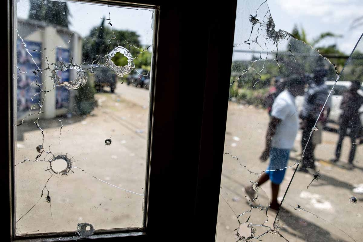 This photo taken on September 3, 2016 in Libreville shows bullet holes in the window of a guard post on the gate of Gabon's opposition leader Jean Ping's headquarters.
