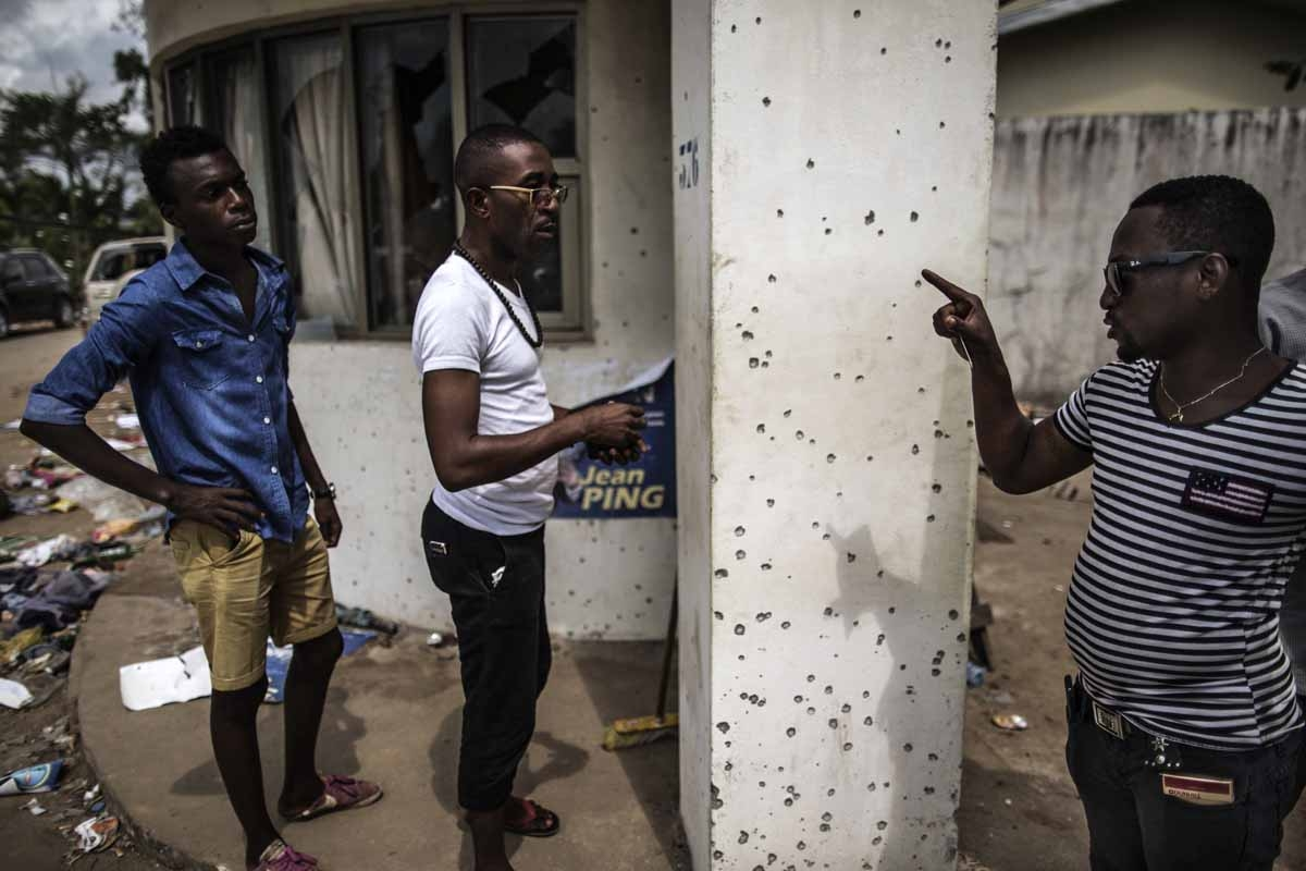 A man points out bullet holes at Gabon's opposition leader Jean Ping's headquarters on September 3, 2016 in Libreville.