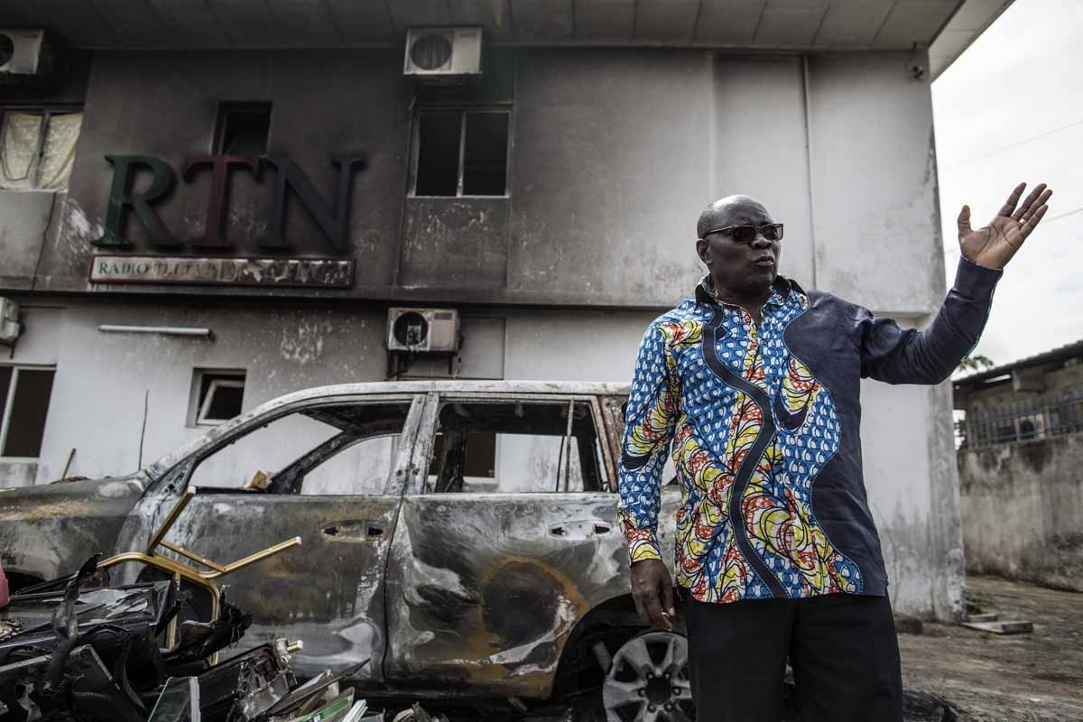 Pastor Georges Bruno Ngoussi, the CEO of the RTN (Radio Television Nazareth) gestures in front of the charred remains of his car in the courtyard of the studios on September 4, 2016 in Libreville.